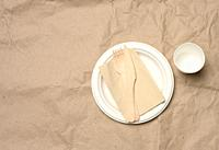 disposable round white paper plate and cup on brown paper background, top view.