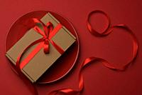 rectangular brown cardboard box tied with a silk red ribbon lies in a round ceramic red plate, top view.