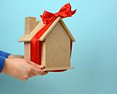 female hands hold a model of a wooden house tied with a red silk ribbon on a blue background, the concept of real estate purchase, mortgage.