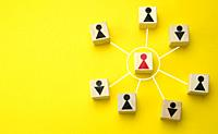wooden cubes with little men on a yellow background. The concept of the structure of the company with a hierarchical scheme, effective business manage...