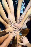 Female Team Mates Show Solidarity Prior to high School Volleyball Match by holding hands.