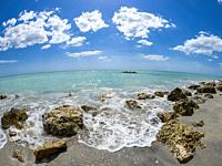 Small waves breaking amoung rocks on the shore of the Gilf of Mexico at Caspersen Beach with blue sky and white clouds in Venice Florida USA.