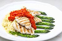 grilled poultry meat with baked red pepper sauce and green asparagus.
