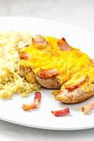 poultry meat baked with bacon and cheese served with couscous.