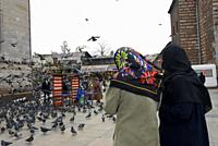 Traveling around Istanbul. Women walking with their heads covered by a hijab near the New Mosque surrounded by pigeons.