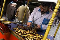 Traveling around Istanbul. seller in cart of roasted chestnuts on a street in Istanbul.