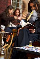 Traveling around Istanbul. Young man smoking shisha and reading a book while having tea.