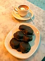 Cup of coffee with three palmeritas, puff pastry and chocolate cakes. Spain.