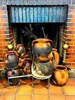 Ceramic pots by a hearth.