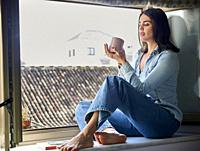 young woman having breakfast at the window