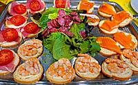 A plate of mixed cold cuts of salmon, sausage and sausage make up an apero snacks plate to be served before a meal.