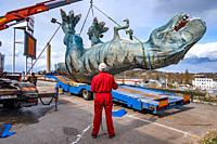 Stockholm, Sweden A large dinosaur figure is dismantled from a shopping mall amusement centre parking lot, (out of business) and is mounted on a truck...