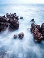 Long exposure severe sea waves rocky coastline in Lovran Croatia