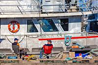 Men on a floating dock taking a break from working on a fishing boat in Steveston Harbour British Columbia Canada.