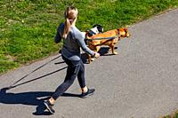 Young woman walking her two dogs on a pathway in Steveston British Columbia Canada.