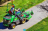 Industrial lawnmower being driven on a pathway in Steveston British Columbia Canada.