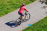 Older woman riding her bicycle along a paved pathway in Steveston British Columbia Canada.