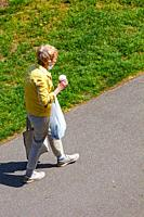 Older woman carrying her coffee cup and bags along a pathway in Steveston British Columbia Canada.