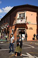Indigenous woman wearing traditional clothing walking in front of the colonial buildings with balconies at the historic center, Quito, Ecuador, South ...