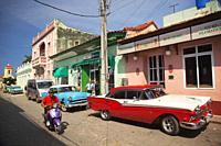 Motorcyclist and old American cars parked in front of the shops at the town center, Trinidad, Sancti Spiritu Province, Cuba, West Indies, Central Amer...