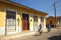 Cyclists in front of the colonial buildings at the town center, Trinidad, Sancti Spiritu Province, Cuba, West Indies, Central America.