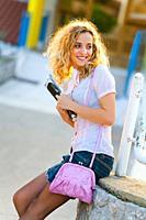 Teenage girl blonde curly hair looking back pleasantly surprised