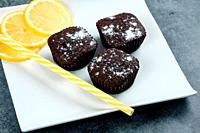 Chocolate cupcakes with lemon slices on a white plate