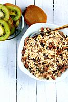 Chocolate muesli bowl with kiwi slices on white wooden board