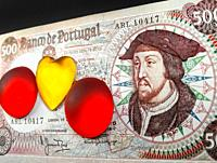 Money bill with the portrait of Joao II king of Portugal and yellow crystal heart and two red crystal circles on black background.