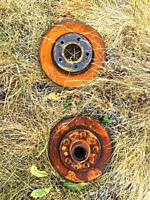 Two wheels rusting in grass, Nova Scotia, Canada.
