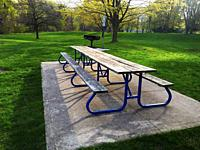 An empty picnic spot in a lovely park with barbecue, a picnic table, and long bench, Ontario, Canada. Covid restrictions keep people away temporarily.