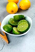 Limes in white bowl with lemons on a stone background