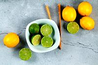 Limes in white bowl with lemons and wooden kitchen utensil on stone background