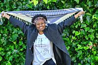 Happy young african woman with an cool hair style and a t-shirt posing outdoor in a garden with a leaves background.
