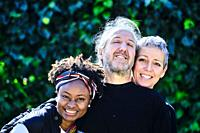 Mature caucasian couple and a young african woman posing hugging outdoor in a family pose in a garden with a leaves background.