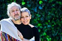 Mature and happy caucasian couple posing hugging outdoor in a garden with a leaves background.