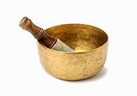 copper singing bowl and wooden clapper on a white background. Musical instrument for meditation, relaxation, various medical practices related to bior...