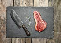 fresh raw piece of beef meat, striploin steak on a wooden background, top view. Marbled piece of meat New York.
