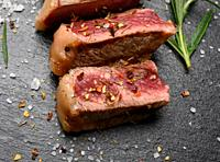 sliced fried beef steak New York striploin on a black background with spices, degree of doneness rare, top view.