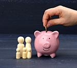 wooden family figurines and pink ceramic piggy bank on blue background. Concept of accumulating cash for buying a house and a car, money in the bank a...