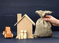 hand holds a canvas bag full of money and a wooden house on a blue background. The concept of buying real estate, renting out. Profitable investment i...