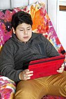 Boy reading a tablet.