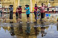 Yangon, Myanmar, Asia - A group of locals scrubs and cleans the floor of the Maha Wizaya Pagoda with brooms and water.