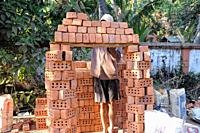 Yangon, Myanmar, Asia - A construction worker piles up bricks onto a wooden board for transport to a nearby building site.