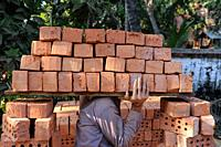 Yangon, Myanmar, Asia - A construction worker carries a stack of bricks on his shoulder to a nearby building site.