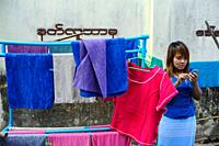 Yangon, Myanmar, Asia - A young woman stands next to a laundry rack with colourful towels and stares at her smartphone.