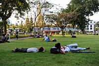 Yangon, Myanmar, Asia - Locals relax on the lawn in the popular Maha Bandula Garden with the Sule Pagoda in the backdrop.