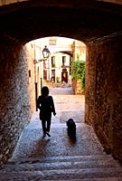 tourist walking in the Arch in the street of Pujada de Sant Domenech, Agullana Palace in the background old town of Girona, Catalonia, Spain.