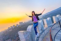 Young woman is pretending to fly before a setting sun scenery
