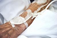 Arm of the patient in the hospital with an intravenous line.